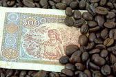 Roasted coffee beans on money background. — Stockfoto
