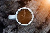 Morning coffee with white cup on the wood charcoal. — Stock Photo