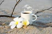 Coffee on the beach and frangipani flower. — Stock Photo