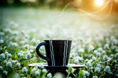 Morning coffee with black cup in the flower grass background. — Stock Photo