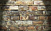 Brown cracked old brick wall lit from above — Stock Photo