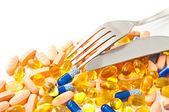 Multi-colored pills and a knife and fork — Stock Photo