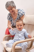 Baby sitting on chair and laughing with grandmother — Stock Photo