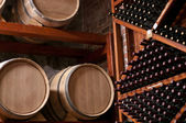 Wine Barrels and bottles on shelf in a Cellar — Stock Photo
