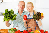 Couple in the kitchen with vegetables. — Stock Photo