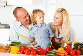 Happy family preparing a healthy dinner at home. — Stock Photo
