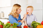 Happy mother with her son in the kitchen — Stock Photo