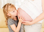 Girl kissing her mother's pregnant belly. — Stock Photo