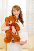 Pregnant woman with teddy bear. — Stock Photo