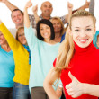 Smiling girl with thumbs up with large group of people on backgr — Stock Photo #44934771