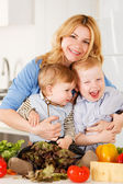 Happy mother with her sons in the kitchen — Stock Photo