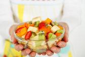 Fruit salad in the hands of women. — Stockfoto