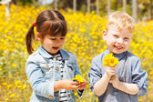 Happy children with yellow flowers. — Stock Photo