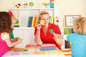 Pre-school children in the classroom with their teacher — Stock Photo