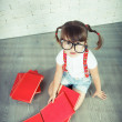 Little nerd girl with glasses and books. — Stock Photo