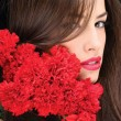 Woman and red carnations — Stock Photo