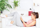 Happy woman with laptop lying on the sofa — Stock Photo