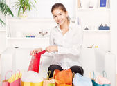 Young woman on couch with shopping bags — Stock Photo