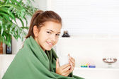 Woman drinking tea at home covered with blanket — Stock Photo
