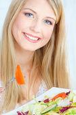 Blond woman eating salad — Stock Photo