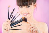 Woman holding set of make up brushes — Stock Photo