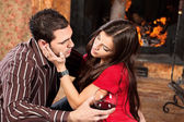 Woman caress her man near fireplace — Stock Photo