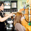 Combing customer's hair — Stock Photo