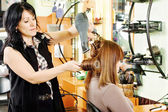 Hairdresser drying customer's hair — Stock Photo