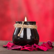 Black candle cup on red background — Stock Photo