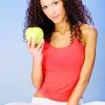Women seating on blue pilates ball holding green apple — Stock Photo #29274749