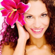 Woman with flower in her curl hair — Stock Photo
