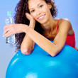 Women behind blue pilates ball holding bottle of water — Stock Photo