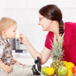 Mother feeding child in kitchen — Stock Photo
