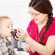 Mother feeding child with grape — Stock Photo