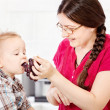 Mother feeding child with grape — Stock Photo #29906485