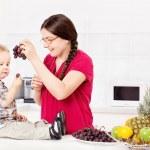 Mother feeding child in kitchen — Stock Photo #29906619