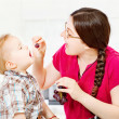 Mother feeding child with grapes — Stock Photo