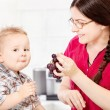 Mother feeding child with grape — Stock Photo #29907397