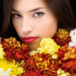Brunette woman behind flowers — Stock Photo