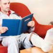 Man with a broken leg on a sofa at home reading book — Stock Photo #7797060