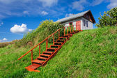 Village house at hill, with stairs — Stock Photo