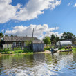 Russian wooden houses at river bank — Stock Photo