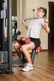 Young man doing lats pull-down workout in gym — Fotografia Stock