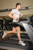 Young man running at treadmill in gym — Stock Photo