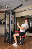 Young man doing lats pull-down workout in gym — Stok fotoğraf