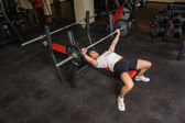 Young man doing bench press workout in gym — Stock Photo