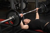 Young man doing bench press workout in gym — ストック写真