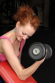 Slim girl doing biceps traning — Stock Photo
