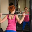 Young girl doing squats with barbell — Stock Photo #45296067