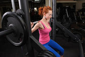 Young girl doing squats with barbell — Stock Photo
